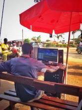 Person in Tanzania browsing the internet on an outdoor desktop computer