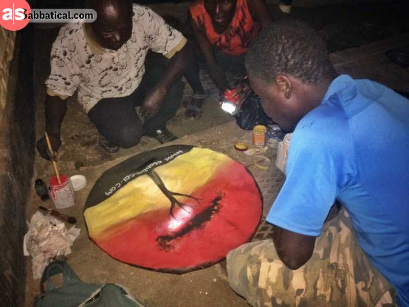 local artists (fishermen) are painting the cover of my spare wheel in Malawi