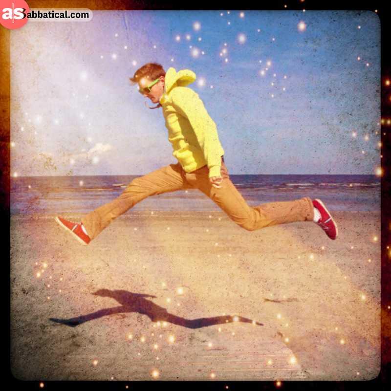 Adrian jumping of joy at the beach of jurmala in latvia at the baltic sea