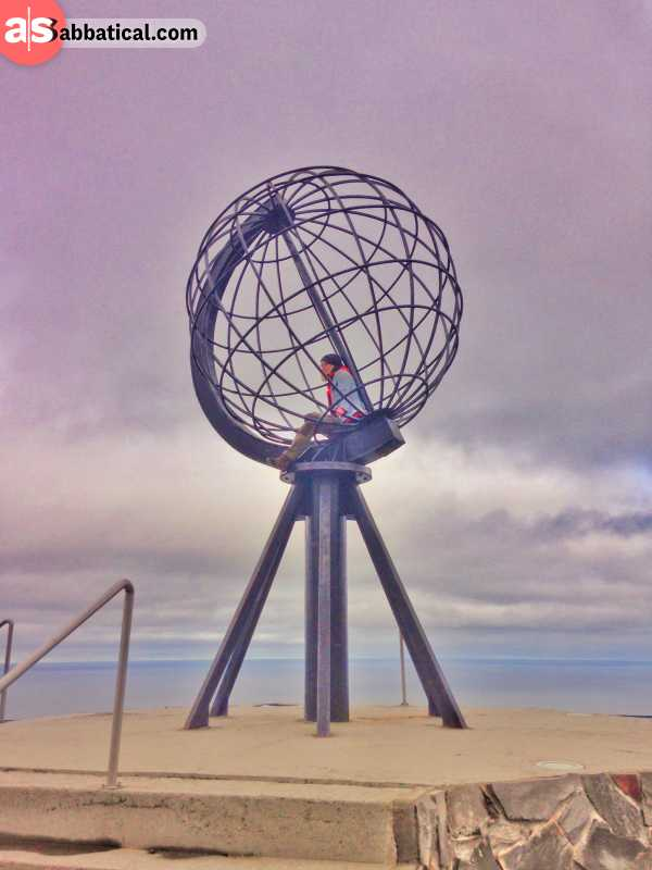 solo traveler inside a globe statue at the North Cape in Norway