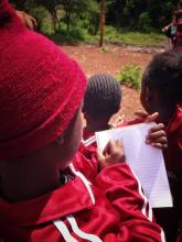 school boy in kenya taking notes - representing travel journey notes