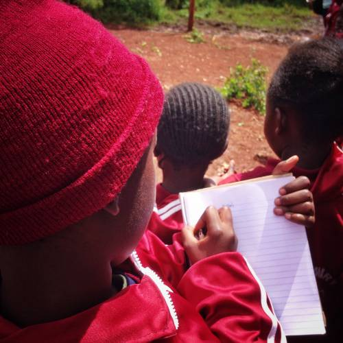 School boy in Kenya taking notes.