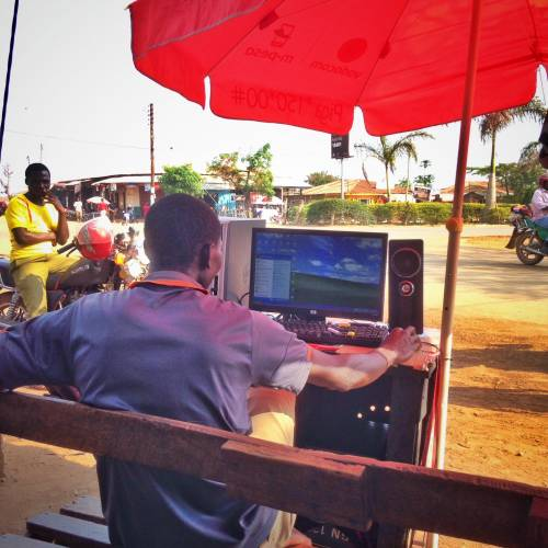 Person in Tanzania browsing the internet on an outdoor desktop computer
